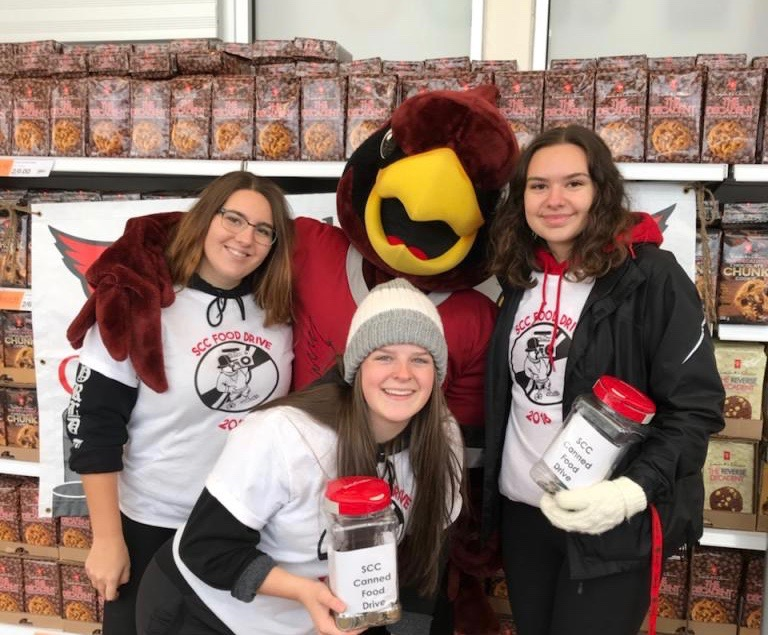 Three students from St. Charles College stand with the school mascot alongside piles of canned food donations