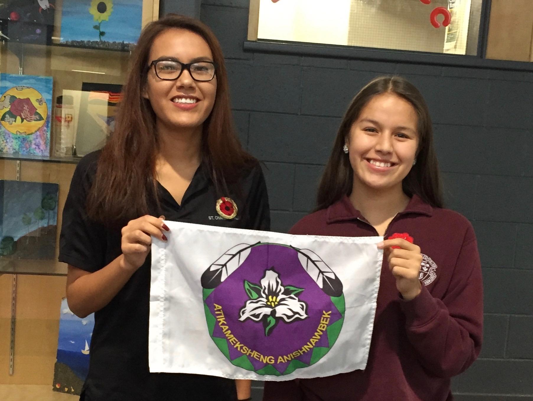 Two students hold the Atikameksheng Anishnawbek flag.